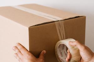 Man taping up a brown cardboard box.