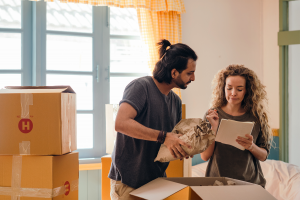 A woman writing a packing list in front of moving boxes while a man looks at list over her shoulder.