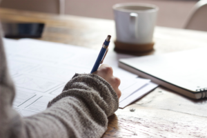 A person signing documents with a pen on a wood table with a coffee mug in front of them.