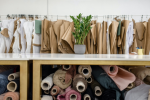 Wood tables with spools of fabric under them, and across from them are clothing racks with paper clothing cutouts.
