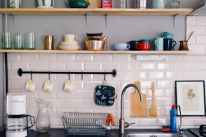 Kitchen with shelves that have assorted bowls and cups and hanging items to enhance household storage space.
