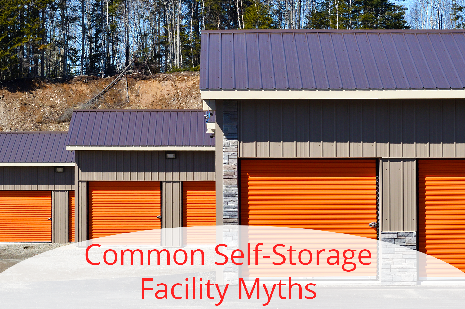 Three self storage facility buildings with orange doors lined up, receding into the back.